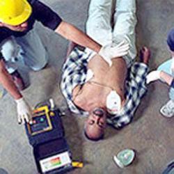 EMT using a defibrillator on man lying down